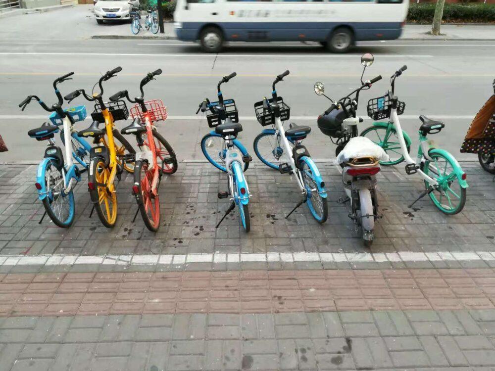 上海の街中にいろいろな種類のシェアバイクが並んでいる様子の写真